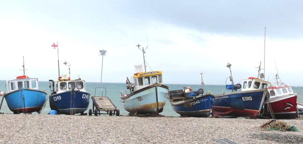 Colourful fishing boats on the shingle beach at Beer.